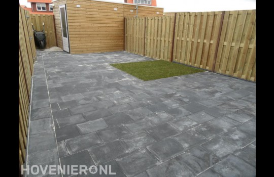 Tuinaanleg met bestrating van betontegels, klein grasveld en schutting