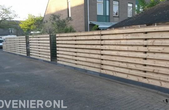 Houten schutting met panelen van betongaas