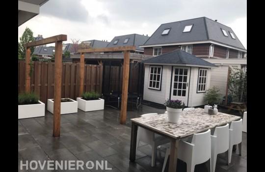 Moderne tuin met bestrating, houten pergola en witte bloembakken